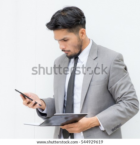 Corporate executive talking on his phone and looking at a book,a serious corporate executive listening on his phone