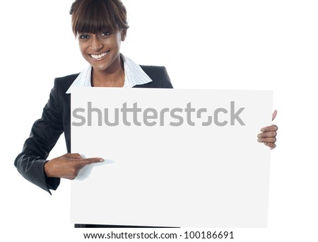 Corporate female executive pointing towards blank banner and smiling at camera