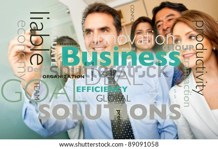 Corporate group writing a graph with business related concepts - stock photo