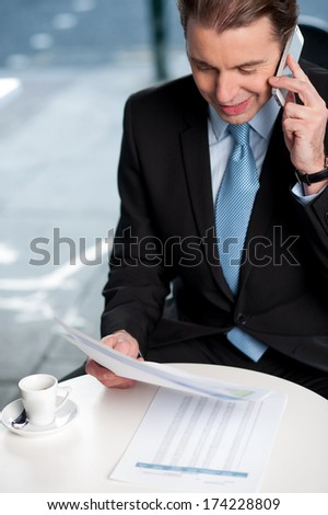Corporate guy discussing reports on phone - stock photo