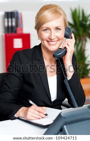 Corporate lady communicating on phone and confirming appointment - stock photo
