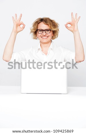 Corporate lady showing excellent gesture to camera sitting in front of laptop