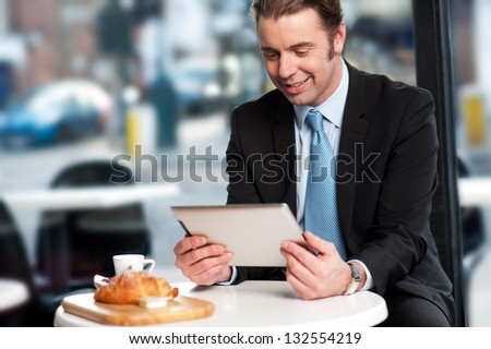 Corporate male manager reviewing business updates on tablet pc while waiting for his order. - stock photo