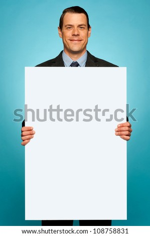 Corporate man holding big white blank billboard isolated over gradient background - stock photo