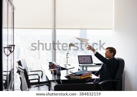Corporate manager in modern office takes a break and prepares a paper airplane. The bored man dreams of his next vacations and leans back on his chair. Copy space - stock photo