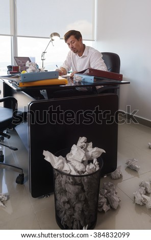 Corporate manager in modern office tries to write a job letter. The man is frustrated and keeps on throwing paper on desk and trash bin - stock photo