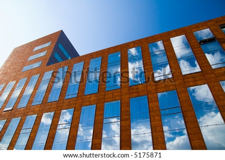 corporate office building windows reflecting white clouds and blue sky