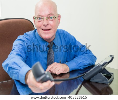 Corporate office worker handing phone towards camera