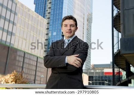 corporate portrait of young attractive businessman in suit and tie standing outdoors in exterior urban office buildings area looking successful and confident - stock photo