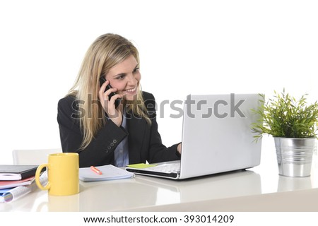 corporate portrait young happy Caucasian blond business woman working talking on mobile phone at office computer desk smiling confident in successful female executive concept