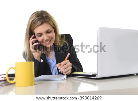 corporate portrait young happy Caucasian blond business woman working talking on mobile phone at office computer desk smiling confident in successful female executive concept - stock photo