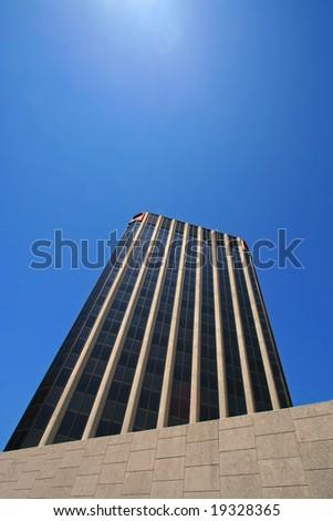 corporate skyscraper perspective against blue sky - stock photo