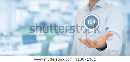 Corporate social responsibility (CSR) concept. Businessman hold virtual label with text CSR, wide banner composition and office in background. - stock photo