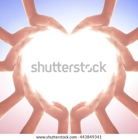 Corporate social responsibility (CSR) concept: Many people hands in shape of heart on blurred beautiful new day background.