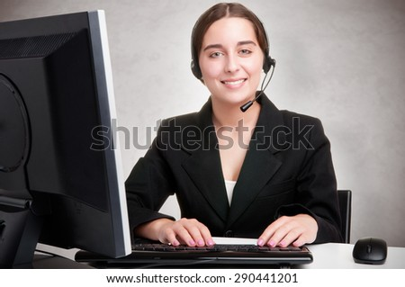 Corporate woman talking over her headset, isolated in a white background