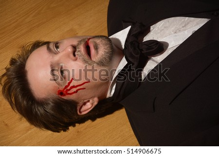 Corpse of killed business man lying on a floor in a bedroom