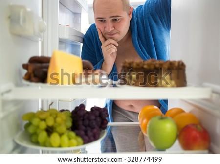 Corpulent man wish hard food rather than healthy food - stock photo