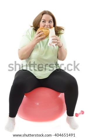 Corpulent woman having addiction to unhealthy food, eating high calories food sitting on fitness ball - stock photo