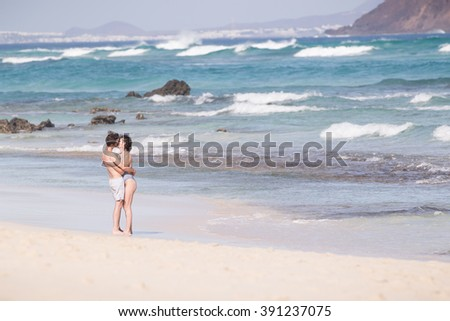 Corralejo, Spain - DEC 18, 2015: Young couple kissing, enjoying vacations on El Corralejo beach, famous holiday destination on Fuerteventura, Canary Islands, Spain on December 18th, 2015.