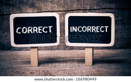 Correct or incorrect. Correct or incorrect written on small blackboards on wooden background - stock photo