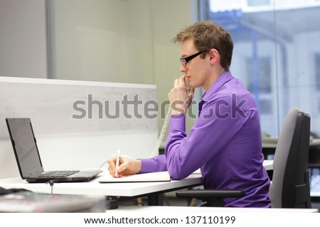 correct sitting position  - Young businessman caucasian in his office on phone making notes - stock photo