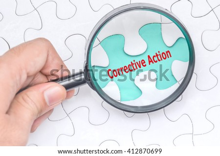 Corrective Action word with hand holding magnifying glass over jigsaw puzzle. Selective focus. - stock photo