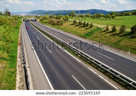 Corridor highway with the transition for animals, in the distance three red car, in the background the city and forested mountains, view from above - stock photo