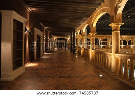 Corridor of an old cloister converted in a modern hotel at night - stock photo