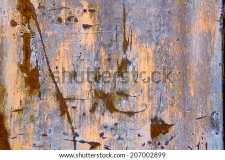 Corroded weathered metal background texture with remnants of colored paint in pink and blue with rusty scratches and a pitted surface