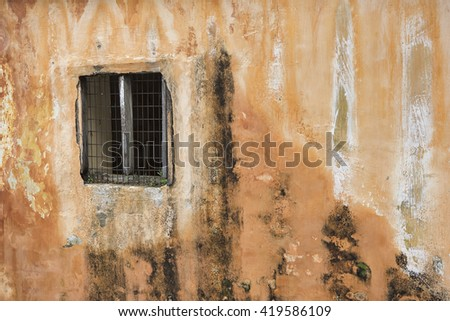 Corrosion and mold covered orange cement wall with a window - stock photo