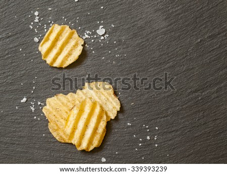 Corrugated potato chips with sea salt on black stone background, top view - stock photo