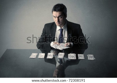 Corrupted businessman counting out some banknotes - stock photo
