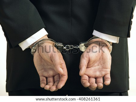 Corruption and bribery theme: businessman in a black suit with handcuffs on his hands on a white background in studio isolated - stock photo