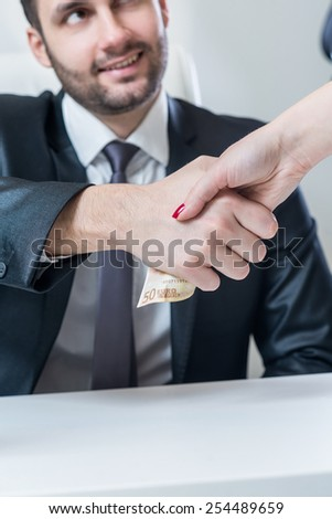 Corruption. Close-up of business woman giving money to another businessman while handshaking. - stock photo