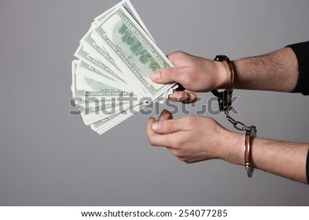 Corruption. hands in handcuffs hold money arrested isolated on white background - stock photo