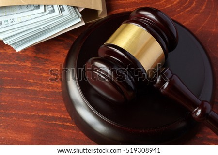 Corruption in a court concept. A gavel and money on a table.