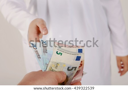 Corruption in Health Care Industry, Doctor receiving Euro banknotes as a bribe. - stock photo
