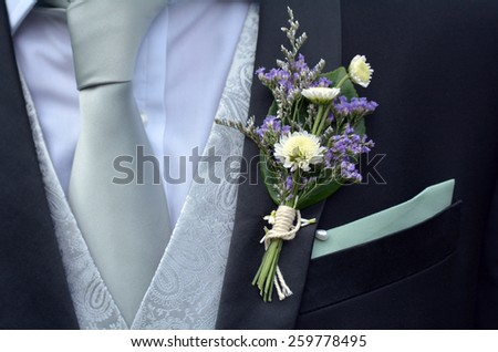 Corsage boutonniere brooch on a man groom suit on wedding day. Wedding men fashion - stock photo