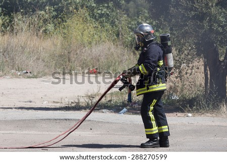 CORSE, FRANCE - CIRCA SEPTEMBRE 2010: Firefighter in action to extinguish a burning car