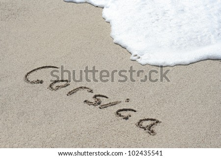Corsica hand written in the sandy beach - stock photo