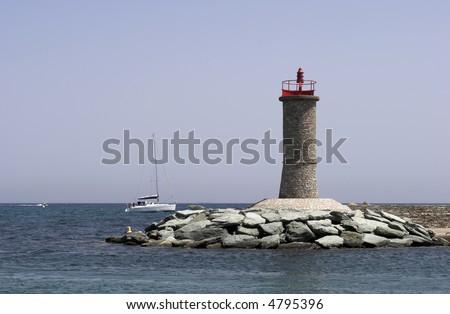 Corsican Lighthouse – Macinaggio in the Mediterranean Sea. - stock photo
