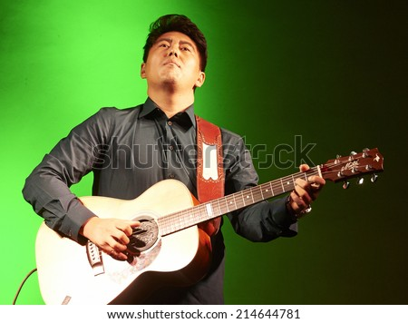 """CORTEFRANCA,ITALY - AUGUST 28:  exhibition live of the  chinese guitar player Joe Zhu at the event """"Acoustic Franciacorta 2014"""",28 August ,2014 in Cortefranca,Italy - stock photo"""