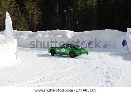 CORTINA D'AMPEZZO, ITALY - FEBRUARY 21: A green and black Porsche 911 ST takes part to the WinteRace classic car race on February 21, 2014 in Cortina d'Ampezzo . This car was built in 1972. - stock photo
