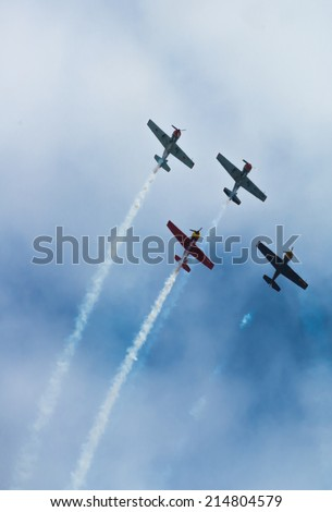 Coruna, Spain - July 17, 2014: Four planes model Yak-52 flying down in formation under a cloudy sky and leaving a smoke trail.
