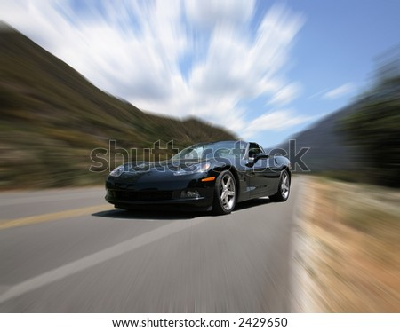 Corvette Speeding on a Mountain Road With Intentional Radial Blur - stock photo