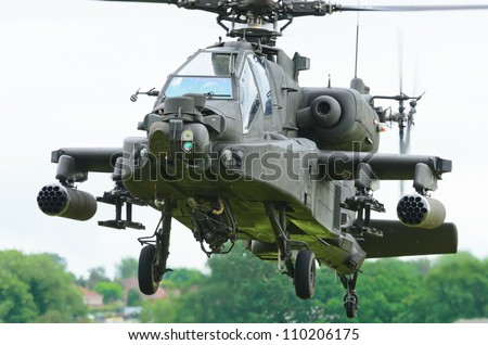 COSFORD, SHROPSHIRE, ENGLAND - JUNE 17: Boeing AH-64 Apache attack helicopter taking off for display on June 17, 2012 in Cosford, Shropshire, England. - stock photo