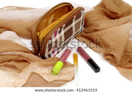 Cosmetic bag and tools for make-up on beige kerchief - stock photo