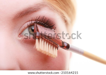 Cosmetic beauty procedures and makeover concept. Closeup part of woman face eye makeup detail. Using comb to separate lashes after applying mascara, long eyelashes. - stock photo