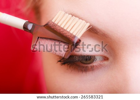Cosmetic beauty procedures and makeover concept. Closeup part of woman face eye makeup detail. Using brush to give brows shape. - stock photo