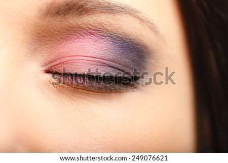 Cosmetic beauty procedures and makeover concept. Closeup part of woman face makeup detail. Eye with color eyeshadows
